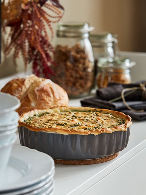 A quiche in a metal pie dish, placed on a sideboard with glass jars in the background.