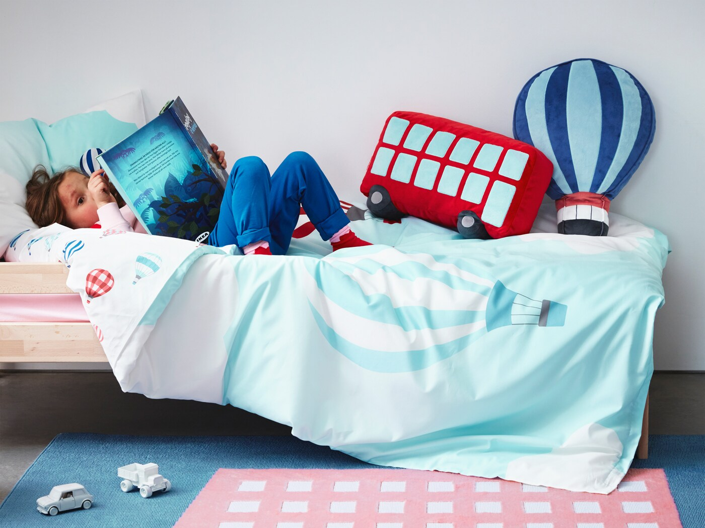 A quilt cover, rug and cushions from UPPTÅG children's textile collection with colourful graphics based on travelling.