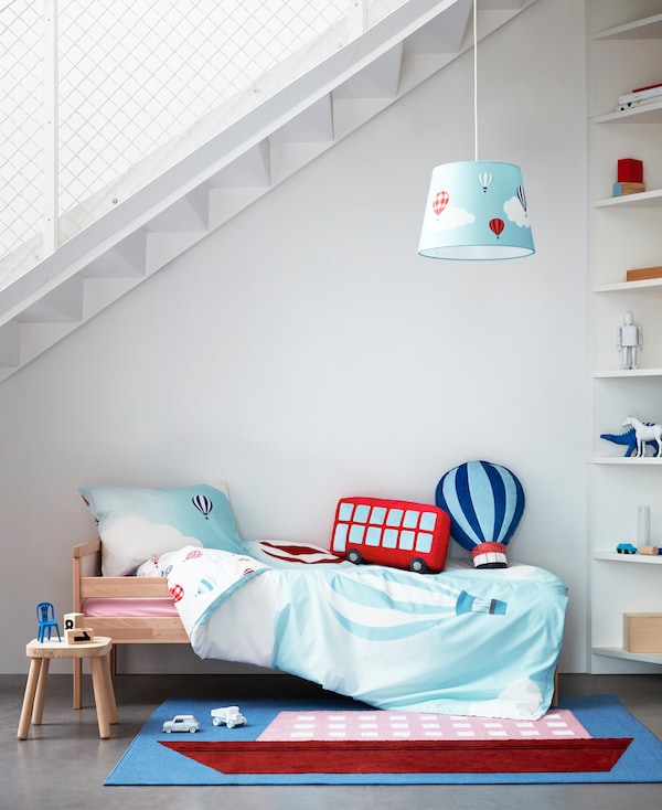 A quilt cover, rug, lamp and cushions from UPPTÅG children's textile collection with colourful graphics about travelling.