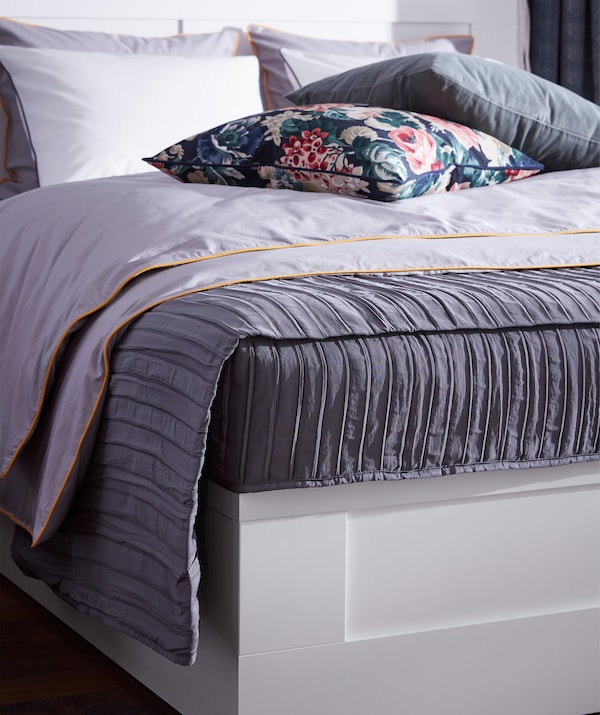 A quilted, lilac IKEA VEKETÅG bedspread with a pleated surface laying on a bed.