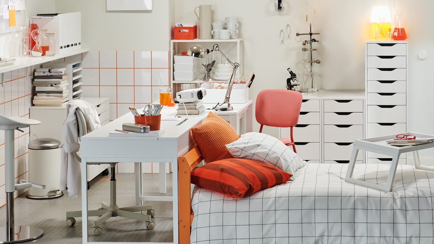 A quirky student room in white and orange furnished with a bed, desk, drawer units, shelves, a bar table and bar stool.