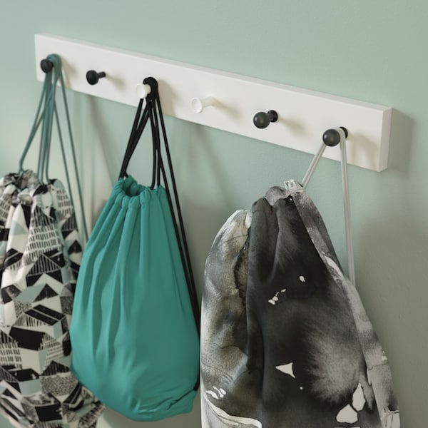 A rack with different styled knobs holding children's gym bags.