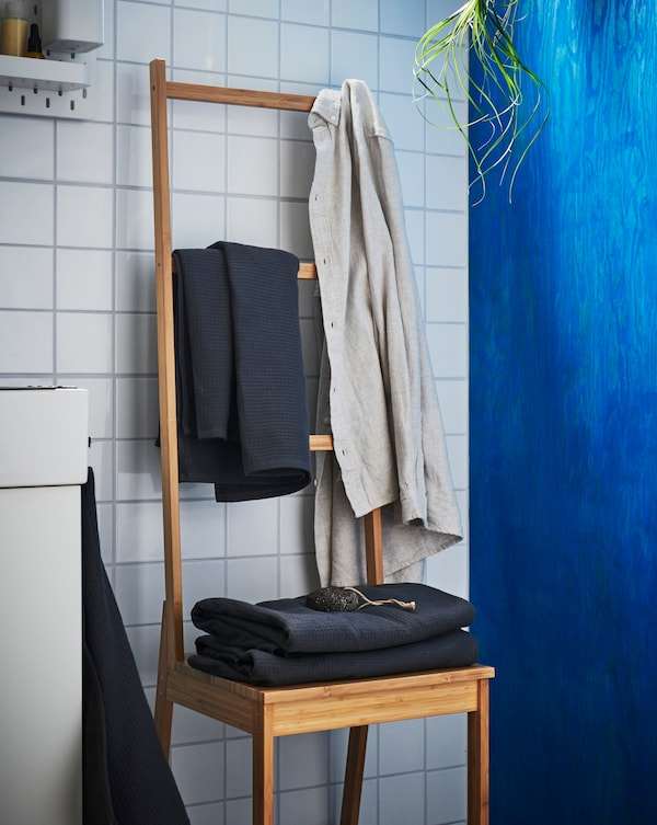 A RAGRUND bamboo towel rack in a white tiled bathroom with gray towels stored on it.