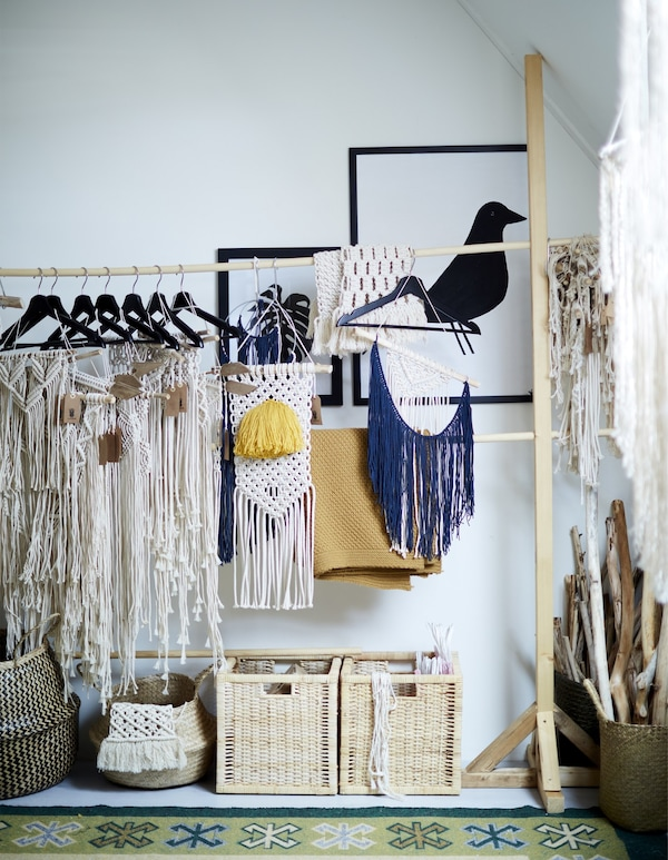 A rail-hanger storage system filled with hanging home-made macramé crafts.