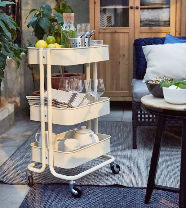 A RÅSKOG kitchen trolley stores a tea set and dishware in a living room.