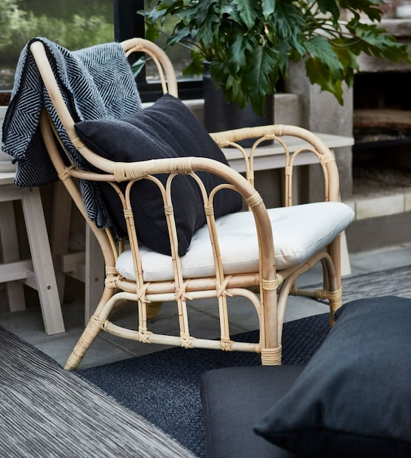 A rattan armchair with a white cushion and black back pillow.