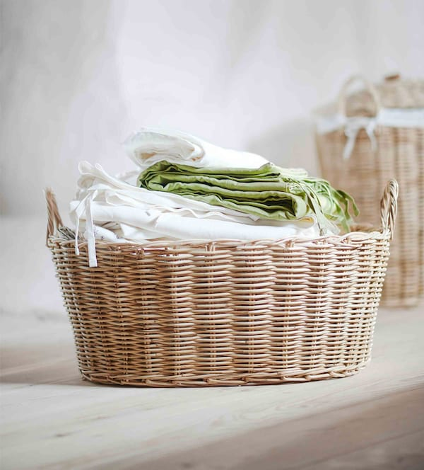A rattan basket piled high with natural-feeling textiles.