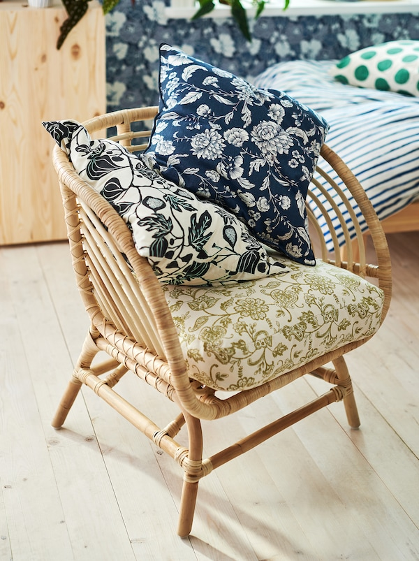 A rattan chair standing in a bedroom with three cushions with slightly different floral patterns in different colours.