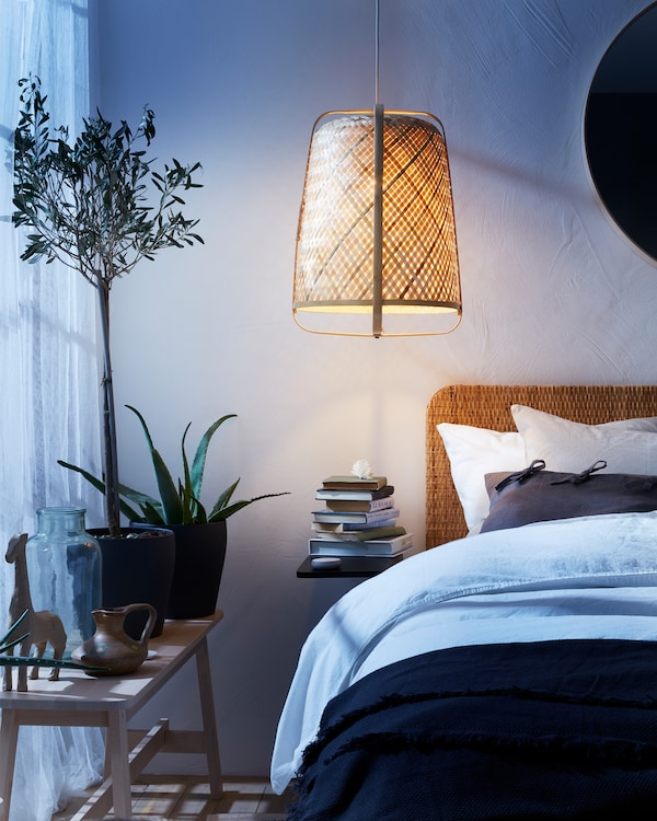 A rattan pendant lamp, a bench, a bed with a rattan headboard, white curtains and different plants in pots.