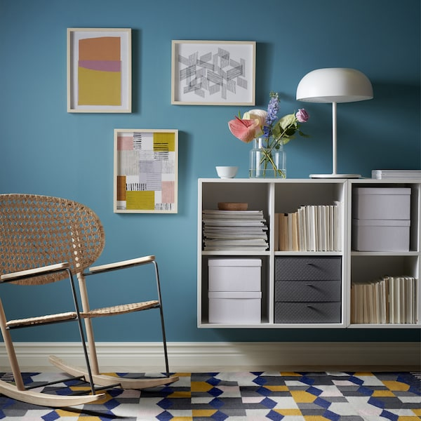 A rattan rocking chair and wall-art beside open storage cube units attached to the wall, with drawer inserts and boxes.
