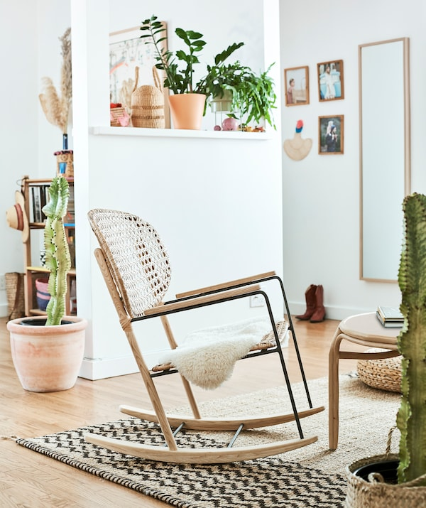 A rattan rocking chair on a hessian rug in a white room, with plants on a shelf and cacti in large pots on the wooden floor.