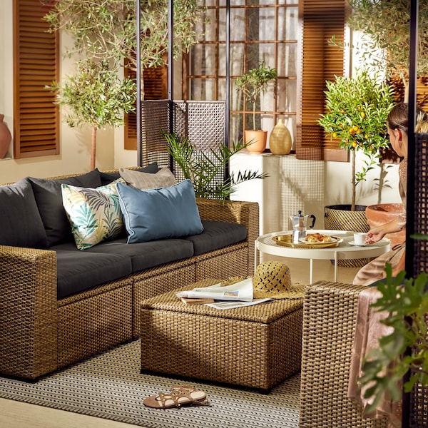 A rattan sofa with black cushions and a rattan coffee table with storage.
