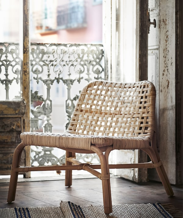 A rattan TÄNKVÄRD chair standing in the doorway of a rustic balcony.