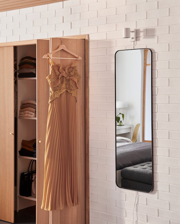 A rectangular mirror with rounded corners is wall-mounted next to a wardrobe, and an orange dress hangs on the wardrobe door.