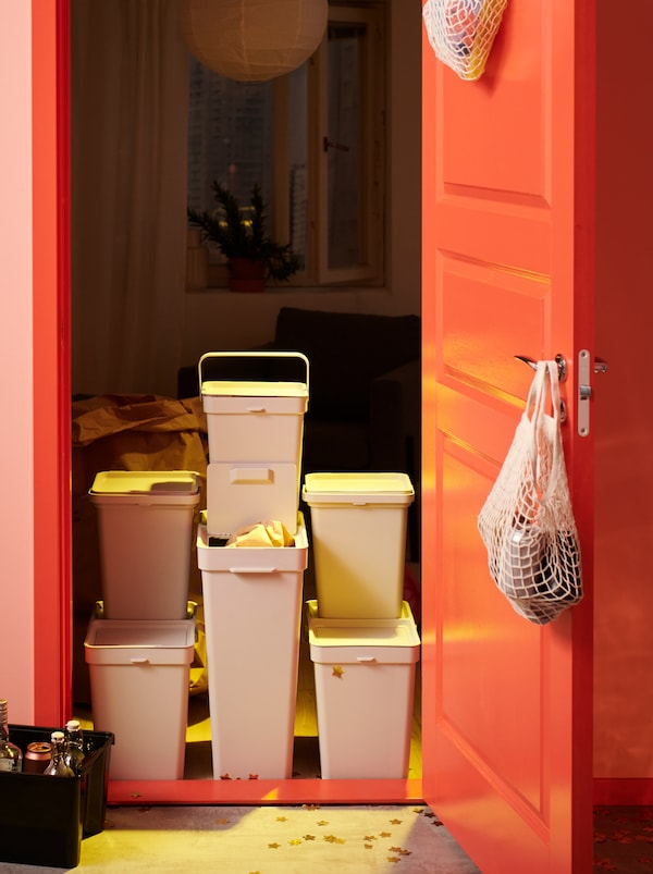 A recycling station made up of various HÅLLBAR bins is placed directly inside a room, its door swung open.