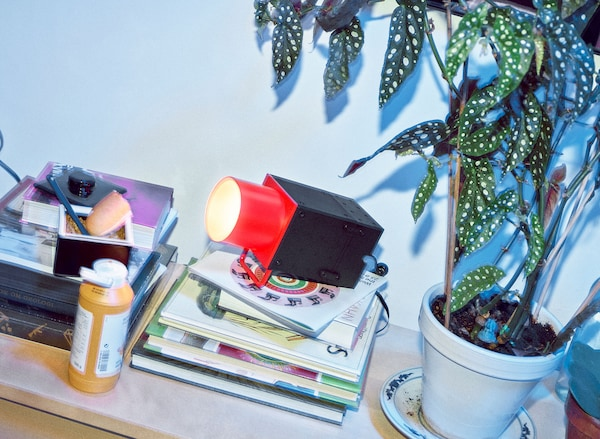 A red and black spotlight sitting on a stack of books with a plant nearby and a bottle of yellow mustard.