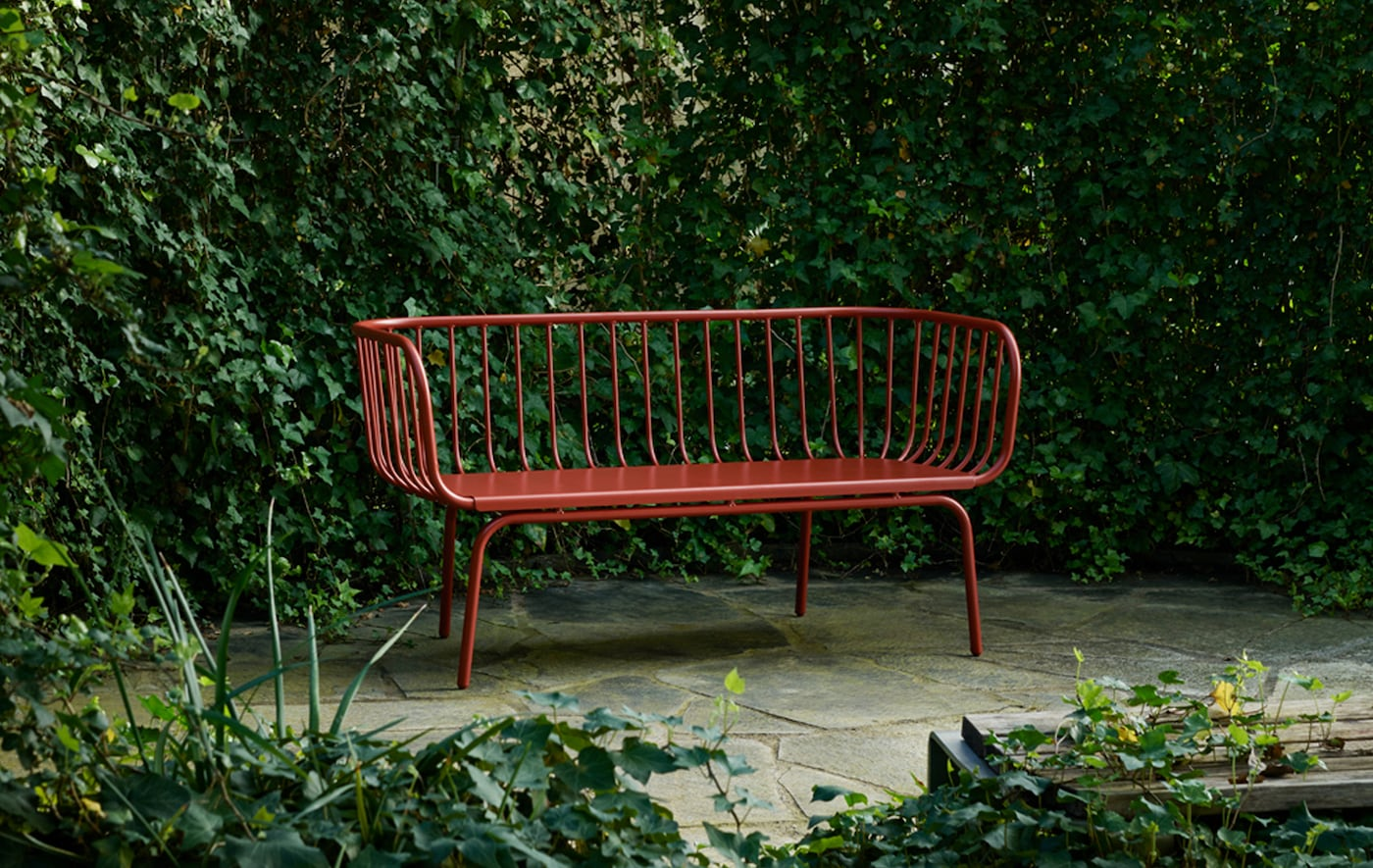 A red bench surrounded by greenery on a paved area.