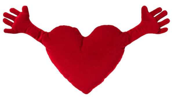 A red heart shaped pillow with arms outstretched against a white background.