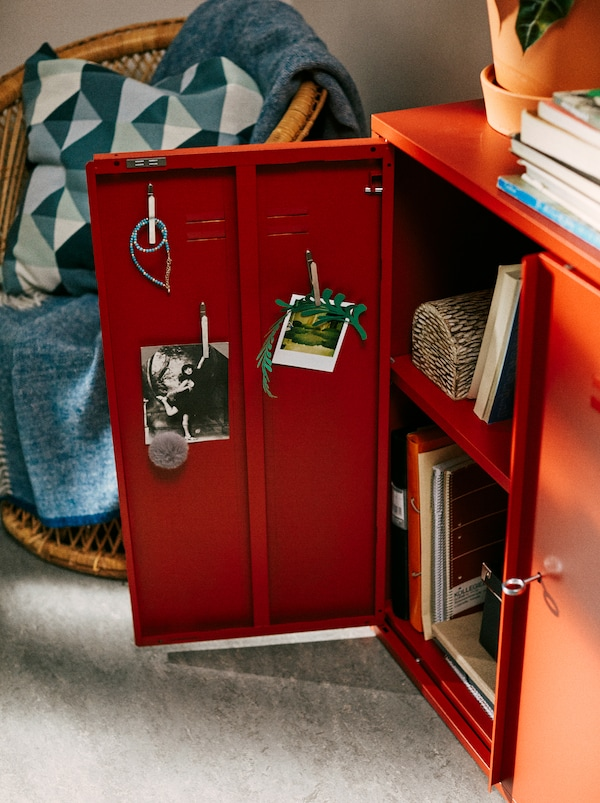 A red IVAR cabinet stands in a student's bedroom, with one door open showing film photos displayed on the inside.
