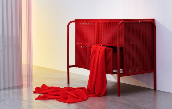 A red metal chest of drawers with four drawers, with a red cloth artfully draped out of one.