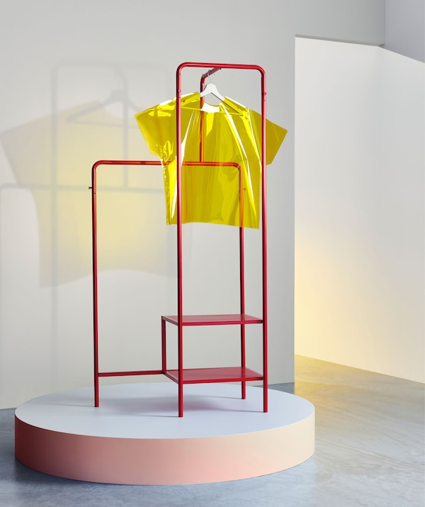 A red metal clothes rack on a podium with a yellow perspex t-shirt hanging from it.