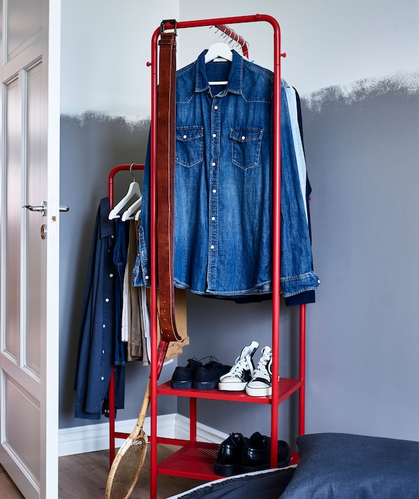 A red metal clothes rail of different heights with shirts and open shoe storage set against a part painted wall.