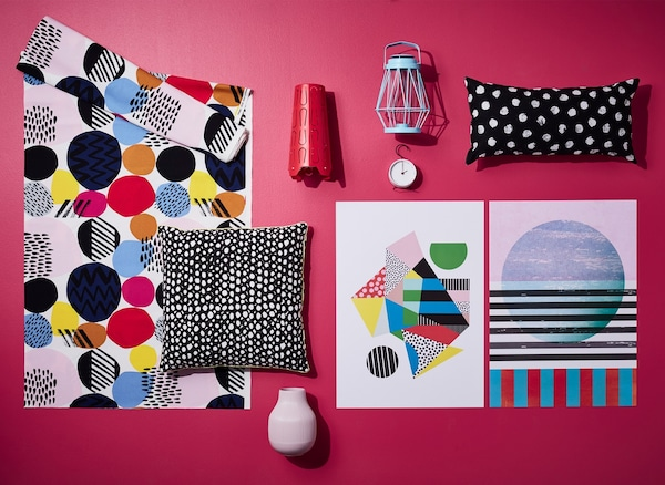 A red mood board scattered with textiles and accessories with strong graphical prints.