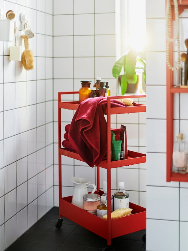 A red NISSAFORS trolley filled with accessories in a white-tiled bathroom also furnished with red and white ENHET modules.