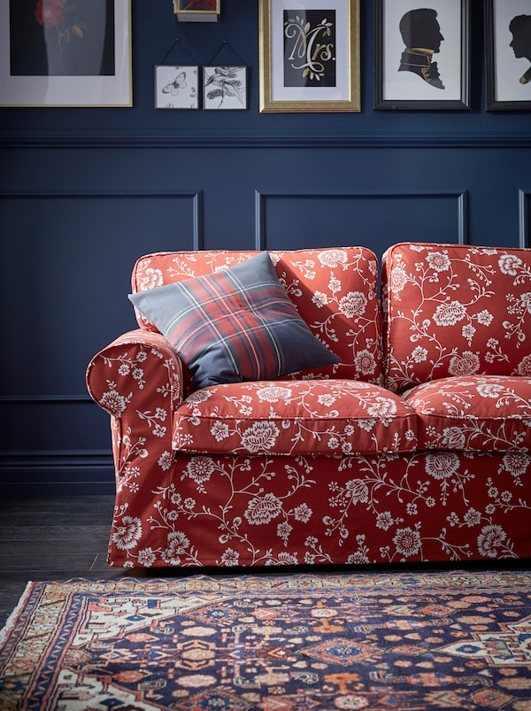 A red, patterned EKTORP sofa with a plaid cushion in a living room with dark, panelled walls covered with framed art.