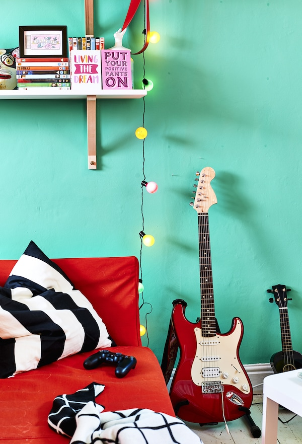 A red sofa and guitar against a green wall.