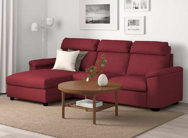 A red sofa in a living room with a round, wood coffee table in front.