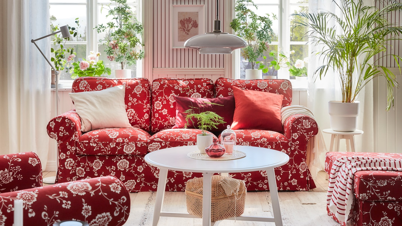A red sofa with white floral design in front of a window, lots of green plants, a round white table and hanging lamp.