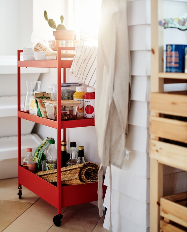 A red trolley on castors stands by a window. Food containers, sauces and bowls stand on the three trolley shelves.