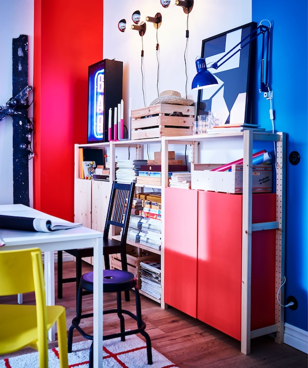 A red, white and blue wall with pine shelving and storage and the corner of a white table with mixed chairs and a stool.