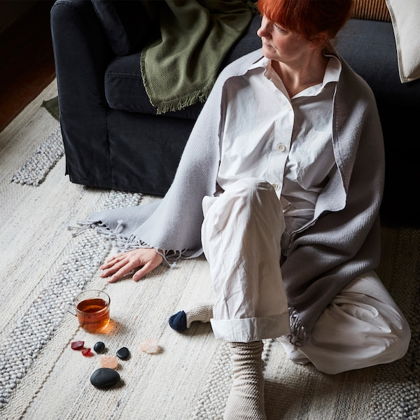 A redhead woman sitting on a rug with a shawl over her shoulders, leaning on the sofa, beside a glass of tea and stones.