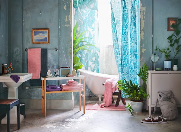 A retro style bathroom setting featuring a white bath with tropical turquoise printed shower curtains and light pink towels.