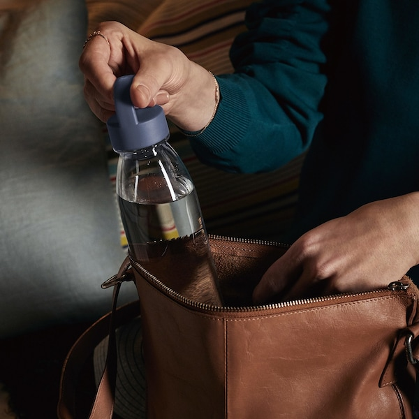 A reusable IKEA 365+ plastic bottle being withdrawn from a brown leather bag.