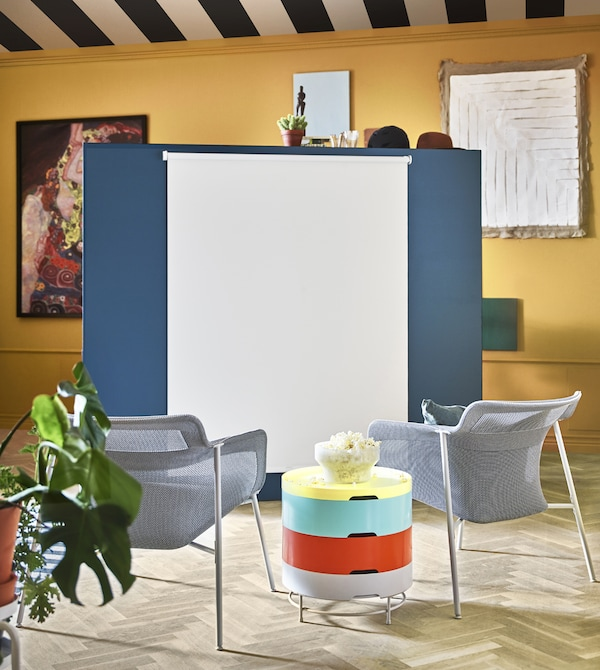 A roller blind attached to a stand-alone wall is pulled down for movie viewing.