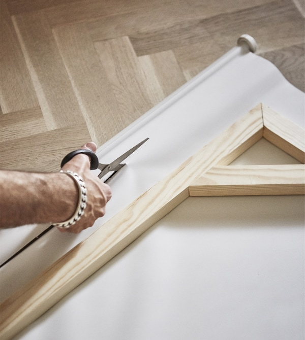 A roller blind is being cut to fit the wooden frame.