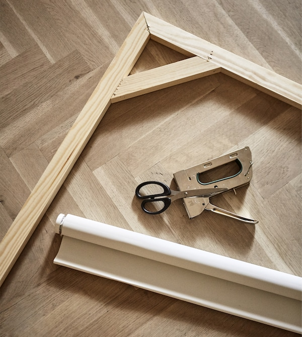 A roller blind, wooden frame, and staple gun lay on a floor.