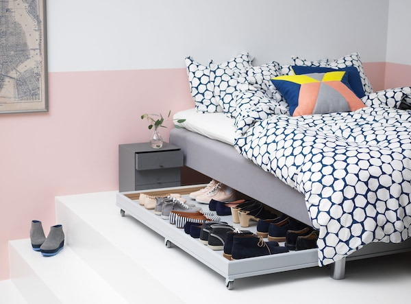 A rolling box that fits under the bed in this white and pink bedroom is filled with shoes.