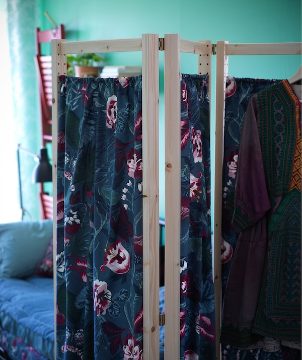 A room dividing screen with wooden frame and texiles.
