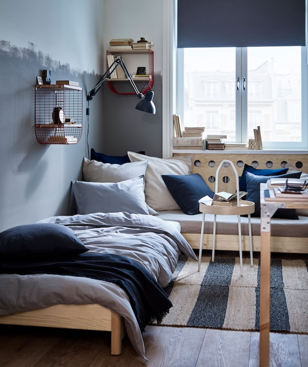 A room with a corner sofa and single bed, with textiles in dark blue, grey and natural colours and red wire wall storage.