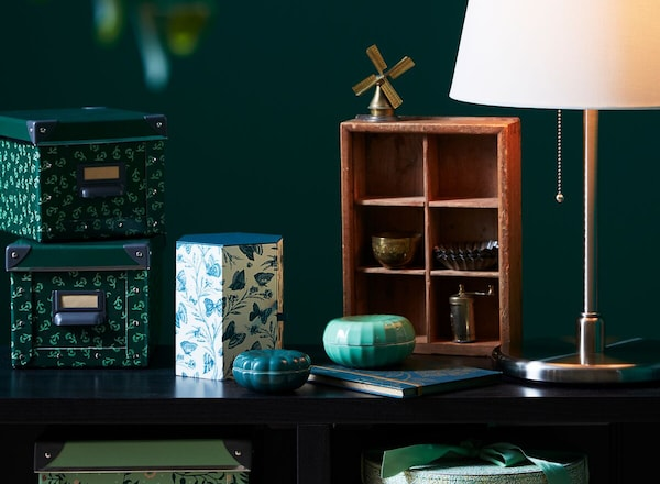 A room with a KALLAX shelving unit, VANLIGEN and ANILINARE boxes, plus a table lamp.