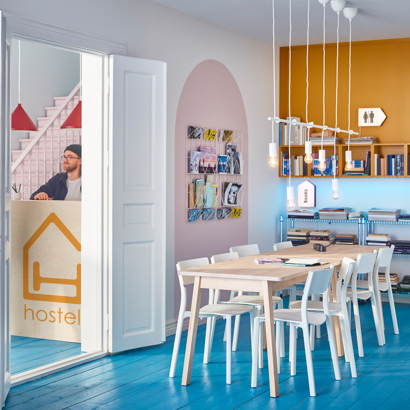 A room with a large wooden table and white chairs in the middle, and wall storage with magazines and books around it.