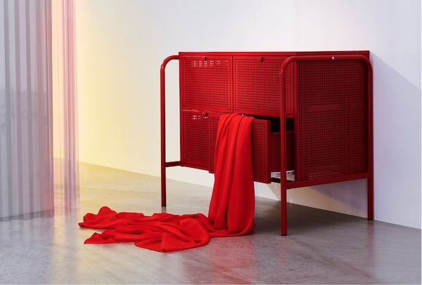 A room with a red NIKKEBY chest of drawers with red fabric draped over one of the open drawers.