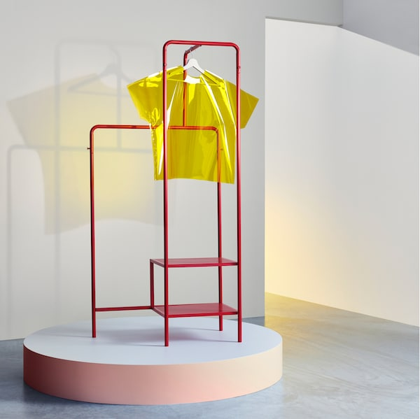 A room with a red NIKKEBY clothe rack and a yellow article of clothing hanging from it on a coat hanger.