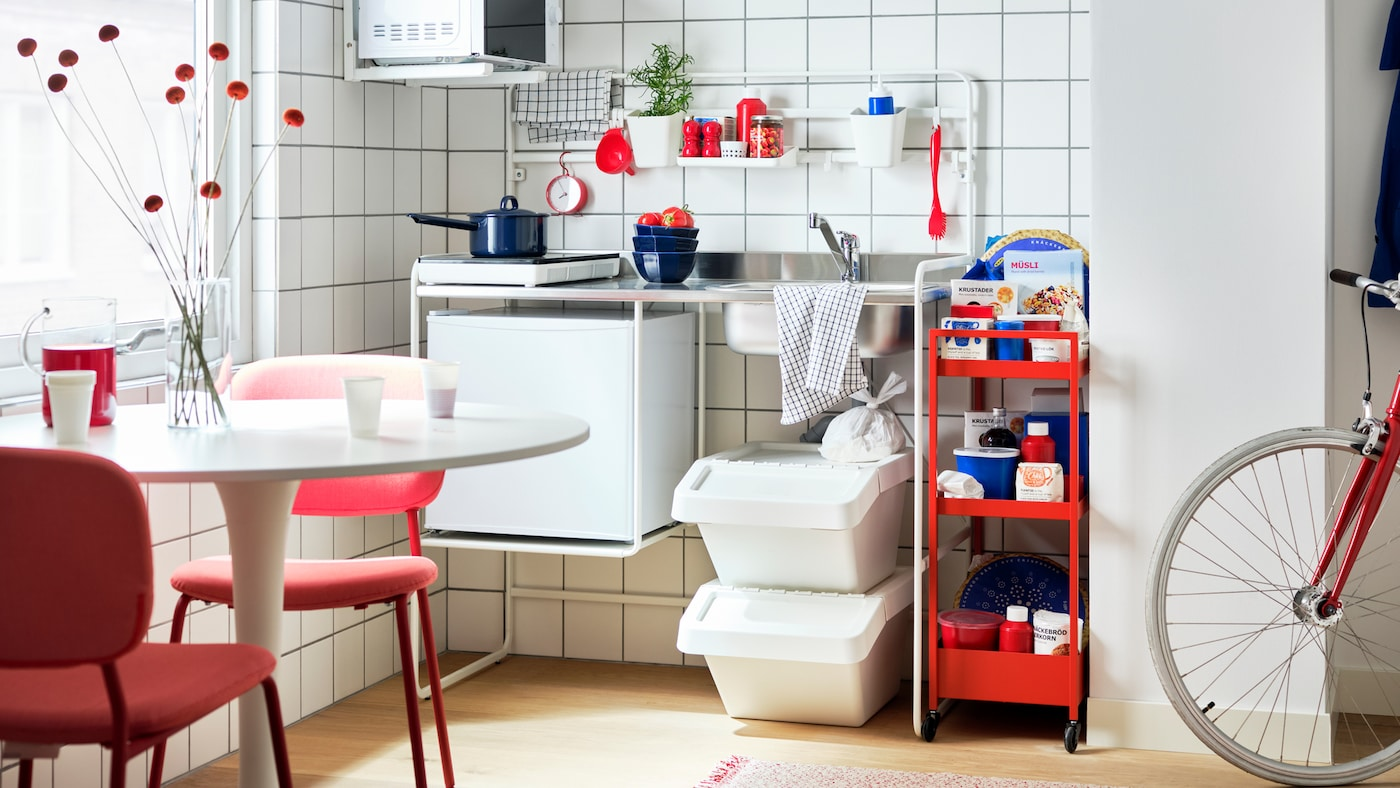 A room with a white SUNNERSTA mini-kitchen, a red trolley, TILLREDA kitchen appliances, a table with red chairs and a bike.