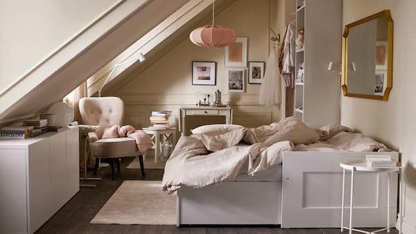 A room with an extended white daybed with light gray/beige bed linen, various storage, a beige armchair and pink pendant lampshade.