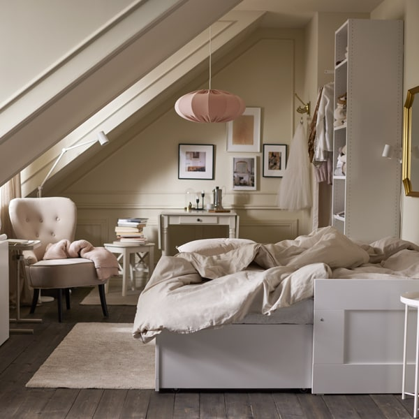 A room with an extended white daybed with light grey/beige bed linen, various storage, a beige armchair and pink pendant.